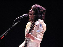 The upper body and face of a female musician. She is wearing a white Victorian-style dress and performing a song on an electric guitar. A microphone is in front of the musician.