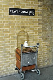 "A sign reading ""Platform 9¾"" with half of a luggage trolley installed beneath, at the interior of King's Cross railway station."