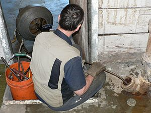 Plumber's snake - A man clears a sanitary sewer pipe with a motorized snake.