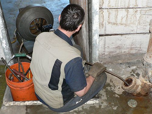 plumber using electric drain snake
