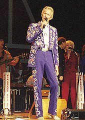 A blond-haired man wearing a blue suit with elaborate patterns on the jacket and the sides of the pants, singing into a microphone