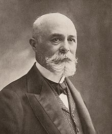 Photo en noir et blanc de la tête d'un homme barbu.