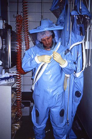 Biosafety level - CDC technician dons an older-model positive-pressure suit before entering one of the CDC's earlier maximum containment labs.