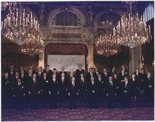 Photo en couleurs d'un groupe sur trois rangées au plafond des grands lustres au fond sur le mur une pancarte que laquelle est écrit CSCE, SOMMET DE PARIS, 19 au 20 juin 1990