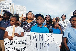 "Hands up, don't shoot - ""Hands up!"" sign at a protest in Ferguson, Missouri in August 2014"