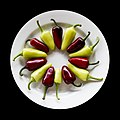 Red and green peppers on white place with black background.jpg