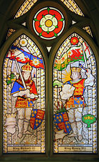 Two men in armour stand opposite each other. They wear crowns and hold swords in their hands. Above the man on the left is a flag of a white boar and a white rose. Above the man on the right is a flag of a red dragon and a red rose. Above and between the two roses is a white rose superimposed on a red rose.