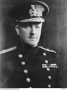Head and shoulders of man in uniform with high collar and peaked cap.