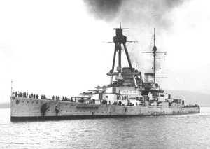 A large gray warship sits motionless in harbor; a line of men are visible on the deck.