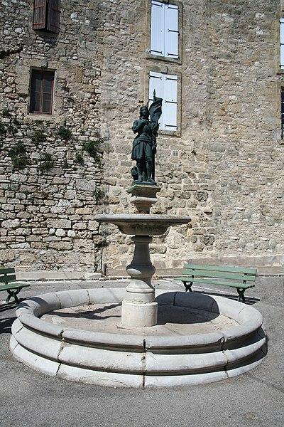 Saint-Pons-de-Mauchiens (Hérault) - Fontaine: Jeanne d'Arc (XIXe siècle). À l'arrière: les remparts.