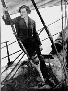 Barrymore, cleanshaven, standing in costume as Captain Ahab, including a false right peg-leg, holding onto ship's rigging