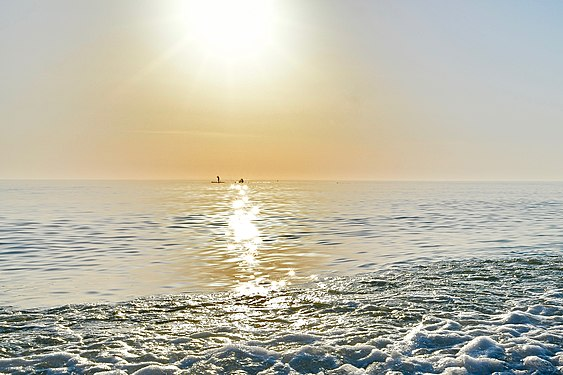 Seascape at sunset with foamy waves in the foreground, a sunny path leading to the horizon and sup-surfers on a sunny path under the sun on the horizon.jpg