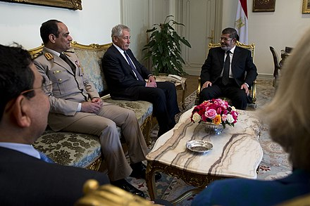 Then President Mohamed Morsi (right) and General al-Sisi (left) listen to visiting U.S. Secretary of Defense Chuck Hagel (center), during a meeting with U.S. officials on April 24, 2013. Al-Sisi, chosen by Morsi to be the first post-Mubarak era Defense Minister, would later sanction the removal of Morsi. Secretary of Defense Chuck Hagel meets with Egyptian President Mohamed Morsy in Cairo, Egypt, April 24, 2013.jpg