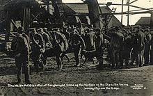 A uniformed stretcher party carry a body away from the pithead; others wait around the pithead. Wreckage from the explosion can be seen in the background.