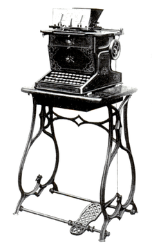 A black typewriter decorated with ornate floral patterns sits affixed to an iron sewing machine stand with a treadle.