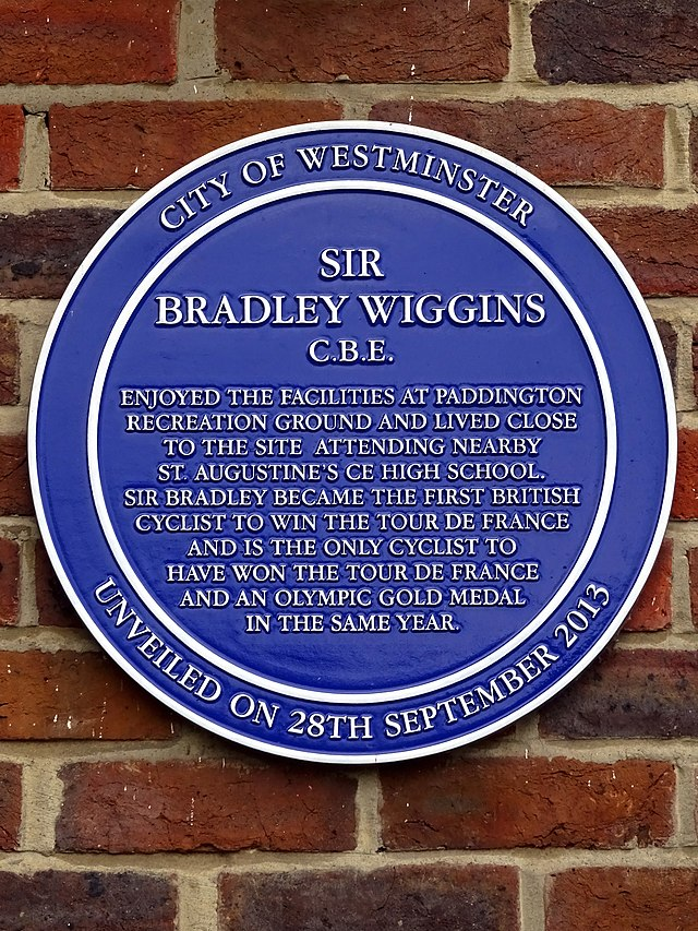 Bradley Wiggins blue plaque - Sir Bradley Wiggins CBE enjoyed the facilities at Paddington Recreation Ground and lived close to the site attending nearby St.Augustine's CE High School. Sir Bradley became the first British cyclist to win the Tour de France and is the only cyclist to have won the Tour de France and an Olympic gold medal in the same year.