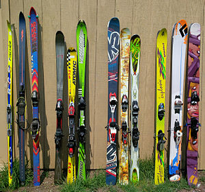 Ski - A collection of differing types of alpine skis, with Nordic and telemark skis at far left. From right: a group of powder skis, a group of twin-tip skis, a group of carving (parabolic) skis, and then an older-type non-sidecut alpine ski along with the non-alpine skis.