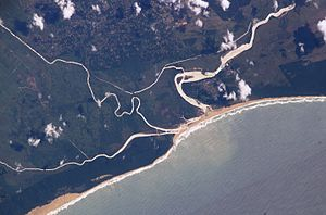 Umfolozi River - The Umfolozi's new and old courses near the mouth. The Msunduzi River enters from the left (south), enclosing a wetland. Note the silt plume in the sea.