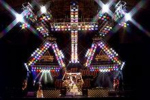 Barevná fotografie kapely Stryper na jevišti pod velkým křížem světel