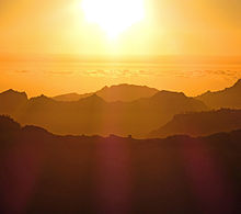 A sky, yellowed by the setting sun, with a mountainous landscape below