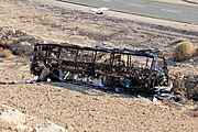 Black frame of a bus lying on gravel ground to the side of a highway road