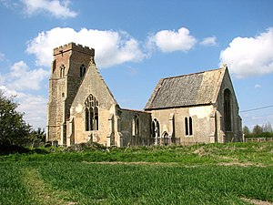 The ruins of a church from the southeast showing from the left a battlemented tower, the gable end of the roofless south transept, and the roofed chancel