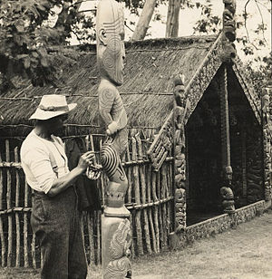 Tiki - A Māori man retouches the painted tattoo on a carved wooden tiki at Whakarewarewa Model Village, New Zealand, 1905.