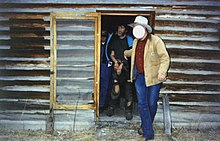 Photograph of a handcuffed Kaczynski being led from a cabin by a man