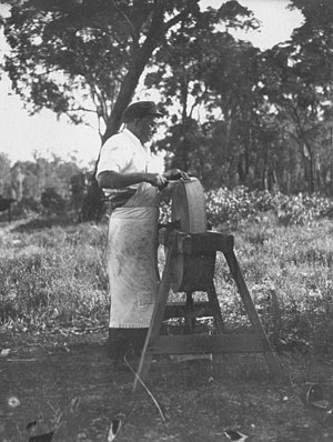 Knife sharpening - A railway camp cook sharpens a knife blade on a stone wheel, 1927