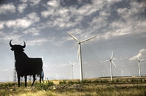 Wind power - Wind turbines are typically installed in favorable windy locations. In the image, wind power generators in Spain, near an Osborne bull.