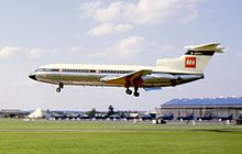 A jet airliner with the letters 'BEA' on the tail fin flies close to the ground from right to left with its undercarriage extended.