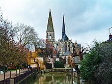Vinterlandskap, delvis nakne trær, med en gotisk kirke, kor med flygende tverrstøtter, overkjørt av et spiss spir også dekket av skifer, og et konisk steint klokketårn;  i forgrunnen et basseng med grønt vann