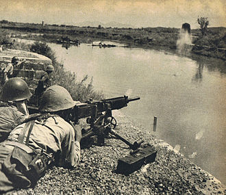Battle of Changsha (1941) - A Japanese soldier firing a Type 92 Heavy Machine Gun across the Miluo river in September 1941