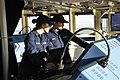 U.S. Coast Guard Petty Officer 1st Class Erin Hunter, right, junior officer of the deck, assists Ensign Katharine Braynard, an underway officer, with monitoring the electronic charting system aboard the seagoing 121127-G-ZZ999-057.jpg