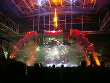 A tour stage; four large legs curve up above the stage and hold a video screen which is extended down to the band. The legs are lit up in red at the top and orange at the bottom. The video screen has multi-coloured lights flashing on it. The audience surrounds the stage on all sides.