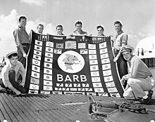 "Black and white photo of eight men in military uniforms holding a large banner with the word ""BARB"" in the center surrounded by Japanese and Nazi flags, symbols designating military medals and symbols signifying bombardments"