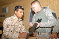 US Army 51038 Sgt. Heriberto Fuentes (right), of Bradenton, Fla., shows an Iraqi Soldier how much dirt and debris is in his weapon during a weapon cleaning session at the Warrior Academy, Sept. 16. Fuentes is an in.jpg