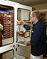 US Navy 030819-N-9593R-096 Hospitalman Randy Connelly, of Breezewood, Penna., feeds a medication bin to the Autoscript III robot at the National Naval Medical Center in Bethesda, Maryland.jpg