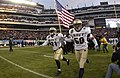 US Navy 031206-N-9693M-532 Navy slot back Tony Lane (21) and line backer Ben Matthews lead the team onto the field holding an American flag prior to the 104th Army Navy Game.jpg