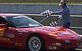 US Navy 040321-N-5862D-206 Cmdr. Brad Neff takes the checkered flag for a victory lap at the Memphis Motor Speedway in the Sports Car Club of America's (SCCA) first national race.jpg