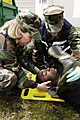 US Navy 050316-N-2101W-001 Lt. Cdmr. Julie Milburn, a family nurse practitioner, left, raises the head of Quartermaster Seaman Joshua Houston, center, as Hospital Corpsman Vincent Falcetta positions a C-collar neck brace.jpg