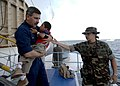 US Navy 070701-N-6278K-140 Lt. Cmdr. Karl Kish, a Navy chaplain, carries a patient into a boat for return home to Guatemala from Military Sealift Command hospital ship USNS Comfort (T-AH 20).jpg