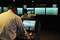 US Navy 080905-N-1831S-005 Operations Specialist 2nd class Dennis Denk navigates the USS Jamestown (NSST 1) a virtual reality ship handling simulator with senior ship handling instructor retired Navy Capt. Jack O'Neill.jpg