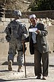 US Navy 081206-N-1810F-102 An Iraqi man pauses to read over a leaflet given to him by a Iraqi National Policeman during a joint U.S. Army Iraqi police walking patrol through the Rashid community in Bahgdad.jpg