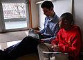 US Navy 090107-N-2013O-011 Gunner's Mate Seaman Shaine Oliver reads to a student at The Sullivans Elementary School at Fleet Activities Yokosuka.jpg