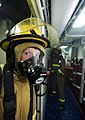 US Navy 090226-N-6538W-244 Damage Controlman Fireman Robert Domozych returns to his hose team after fighting a simulated fire.jpg