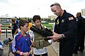 US Navy 090506-N-5366K-049 Lt. Cmdr. Robert Kaminski, assigned to the U.S. Navy Parachute Team the Leap Frogs shows children a display M-4 assault rifle at Dr. Pepper Ball Park after the team parachuted into the park.jpg