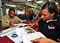 US Navy 090726-N-6233H-024 Chief Navy Counselor Lloyd Stanford, command career counselor for Carrier Air Wing (CVW) 5, explains the Perform to Serve program and conversion packages to Ship's Serviceman Seaman Tia Woodson during.jpg
