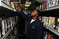US Navy 100130-N-6604E-006 Logistics Specialist Seaman Joshua Williams browses through books in the ship's library aboard the aircraft carrier USS Dwight D. Eisenhower (CVN 69).jpg