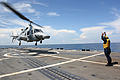 US Navy 110817-N-ZI300-113 Boatswain's Mate 3rd Class James Holmes, a landing safety enlisted, directs an Ecuadorian navy Bell 230 helicopter to ta.jpg